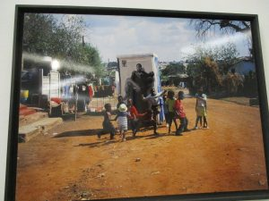 The skinny is sticked on mobile toilet in Africa Town. We can see children playing in front of the photography showing a woman wearing a man. The man seems to be tired and very skinny. The picture is about the raccying against aids in Africa.